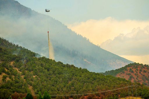 (Anna Stonehouse/The Aspen Times via AP). A helicopter drops a bucket of water it gathered from Lake Christine on a wildfire on Basalt Mountain, in Colo., Friday, July 6, 2018.