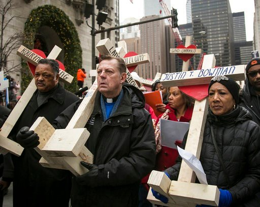(Ashlee Rezin/Chicago Sun-Times via AP). FILE - In this Dec. 31, 2016 file photo, The Rev. Michael Pfleger, center, Rev. Jesse Jackson,  left, and state Sen. Jacqueline Collins, right, led hundreds in a march down Michigan Avenue, carrying crosses for ...
