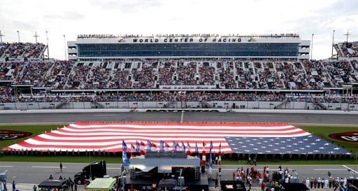 (AP Photo/John Raoux). A U.S. flag covers the infield during the national anthem before the NASCAR Cup Series auto race at Daytona International Speedway, Saturday, July 7, 2018, in Daytona Beach, Fla.