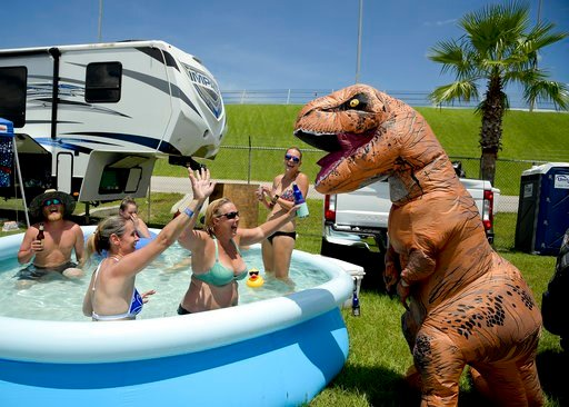 (AP Photo/Phelan M. Ebenhack). Joseph Gullett, right, dressed in a dinosaur suit jokes with fans relaxing in a pool cooling off in a camping area before a NASCAR cup series auto race at Daytona International Speedway, Saturday, July 7, 2018, in Daytona...