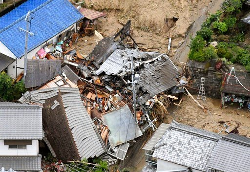(Kyodo News via AP). Residential buildings are damaged by a landslide caused by heavy rains in Sakacho, Hiroshima prefecture, south western Japan, Saturday, July 7, 2018. Torrents of rainfall and flooding continued to batter southwestern Japan.