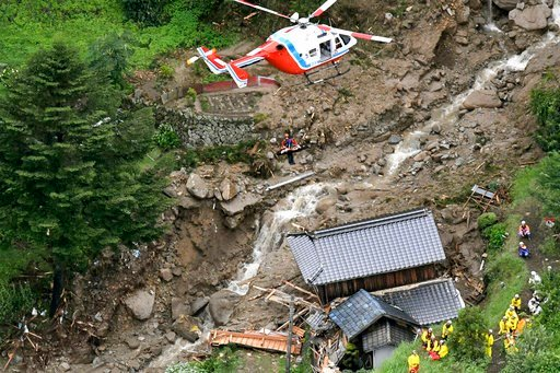 (Kyodo News via AP). A rescue helicopter hovers over damaged buildings after a landslide caused by heavy rains in Iwakuni, Yamaguchi prefecture, southwestern Japan, Saturday, July 7, 2018. Torrents of rainfall and flooding continued to batter southwest...