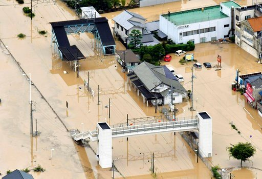(Shingo Nishizume/Kyodo News via AP). Buildings are partially submerged by floodwaters caused by heavy rains in Kure, south western Japan, Saturday, July 7, 2018. Torrents of rainfall and flooding continued to batter southwestern Japan.