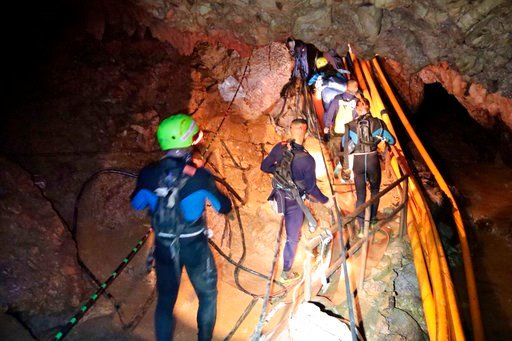 (Royal Thai Navy via AP). In this undated photo released by Royal Thai Navy on Saturday, July 7, 2018, Thai rescue team members walk inside a cave where 12 boys and their soccer coach have been trapped since June 23, in Mae Sai, Chiang Rai province.