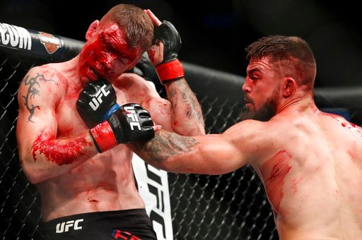 (AP Photo/John Locher). Mike Perry, right, hits Paul Felder during a welterweight mixed martial arts bout at UFC 226, Saturday, July 7, 2018, in Las Vegas.