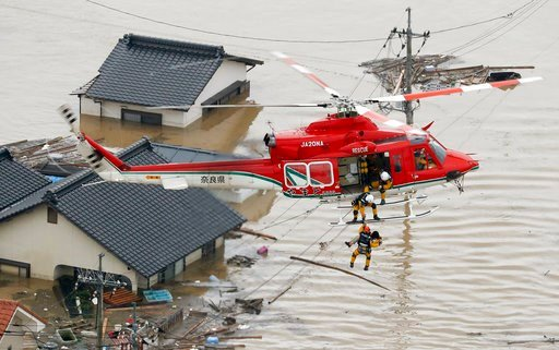 (Shohei Miyano/Kyodo News via AP). In this July 7, 2018 photo, a resident is rescued in a flooded area in Kurashiki, Okayama prefecture, following heavy rain. Heavy rainfall hammered southern Japan for the third day, prompting new disaster warnings on ...