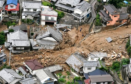 (Koji Harada/Kyodo News via AP). Houses are damaged by mudslide following heavy rains in Kure city, Hiroshima prefecture, southwestern Japan, Saturday, July 7, 2018. Heavy rainfall hammered southern Japan for the third day, prompting new disaster warni...