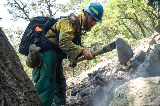 (Anna Stonehouse/The Aspen Times via AP). Oregon firefighter Markus Idroga puts out hot spots above the Wilds neighborhood from the Lake Christine Fire, Sunday, July 8, 2018, in Basalt, Colo.