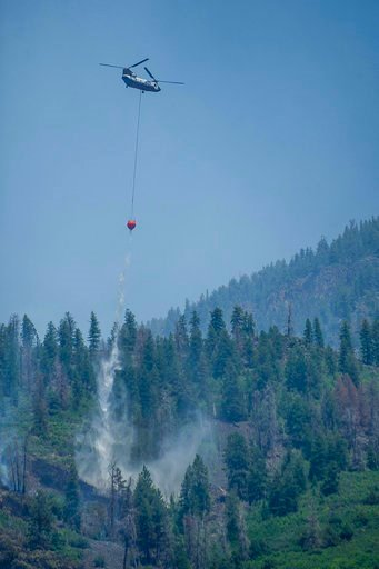 (Anna Stonehouse/The Aspen Times via AP). A Chinook helicopter drops a bucket of water on Basalt Mountain as efforts to fight the wildfires continues, Sunday, July 8, 2018, in Basalt, Colo.