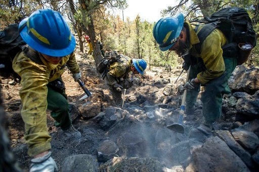 (Anna Stonehouse/The Aspen Times via AP). An Oregon fire crew inspects hot spots from the Lake Christine Fire, Sunday, July 8, 2018, in Basalt, Colo.