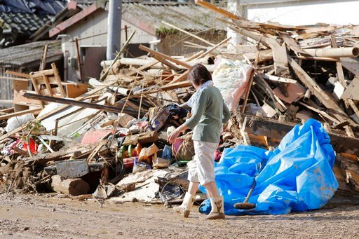 (Takuto Kaneko/Kyodo News via AP). A woman walks past debris caused by a heavy rain in Uwajima, Ehime prefecture, western Japan Monday, July 9, 2018. People prepared for risky search and cleanup efforts in southwestern Japan on Monday, where several da...