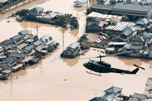 (Kyodo News via AP). A helicopter flies over a flooded housing area in Kurashiki, Okayama prefecture, western Japan Monday, July 9, 2018. People prepared for risky search and cleanup efforts in southwestern Japan on Monday, where several days of heavy ...