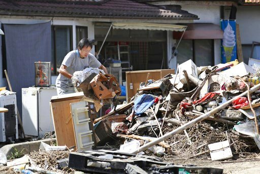 (Takaki Yajima/Kyodo News via AP). A man cleans debris caused by a heavy rain in Soja, Okayama prefecture, western Japan Monday, July 9, 2018.  People prepared for risky search and cleanup efforts in southwestern Japan on Monday, where several days of ...