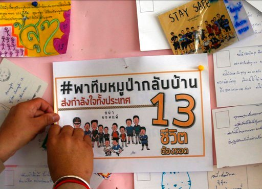 (AP Photo/Sakchai Lalit). A Thai well wisher put poster to pray for boys and their soccer coach who have been trapped since June 23, in Mae Sai, Chiang Rai province, northern Thailand Monday, July 9, 2018.
