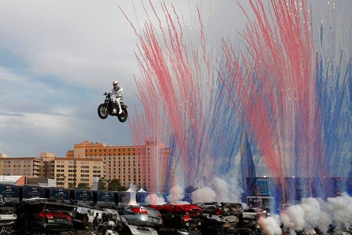 (AP Photo/John Locher). Travis Pastrana jumps a row of crushed cars on a motorcycle, Sunday, July 8, 2018, in Las Vegas. Pastrana is attempting to recreate three of Evel Knievel's iconic motorcycle jumps on Sunday, including the leap over the fountains...