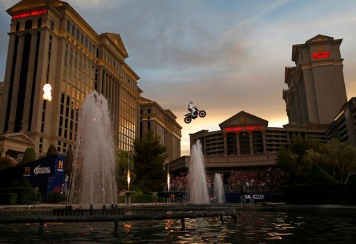 (AP Photo/John Locher). Travis Pastrana jumps the fountain at Caesars Palace on a motorcycle Sunday, July 8, 2018, in Las Vegas. Pastrana recreated three of Evel Knievel's iconic motorcycle jumps on Sunday, including the leap over the fountains of Caes...