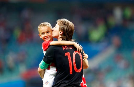 (AP Photo/Rebecca Blackwell). Croatia's Luka Modric, right, celebrates with a child after winning the quarterfinal match between Russia and Croatia at the 2018 soccer World Cup in the Fisht Stadium, in Sochi, Russia, Saturday, July 7, 2018.