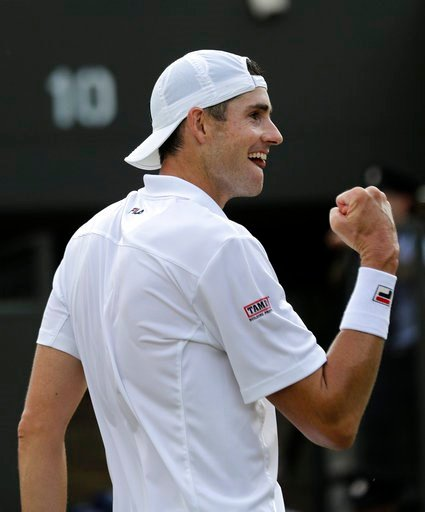 (AP Photo/Ben Curtis). John Isner of the US celebrates defeating Stefanos Tsitsipas of Greece in their men's singles match on the seventh day at the Wimbledon Tennis Championships in London, Monday July 9, 2018.