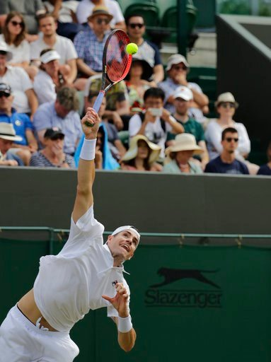 (AP Photo/Ben Curtis). John Isner of the US serves to Stefanos Tsitsipas of Greece during their men's singles match on the seventh day at the Wimbledon Tennis Championships in London, Monday July 9, 2018.