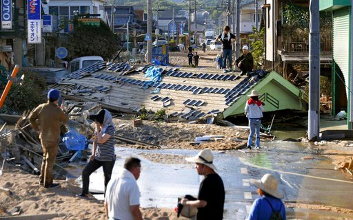 (Yohei Nishimura/Kyodo News via AP). In this Monday, July 9, 2018, photo, a roof of a house is left in the middle of a road in Kurashiki, Okayama prefecture, western Japan. Rescuers in southwestern Japan dug up more bodies Monday as they searched for d...