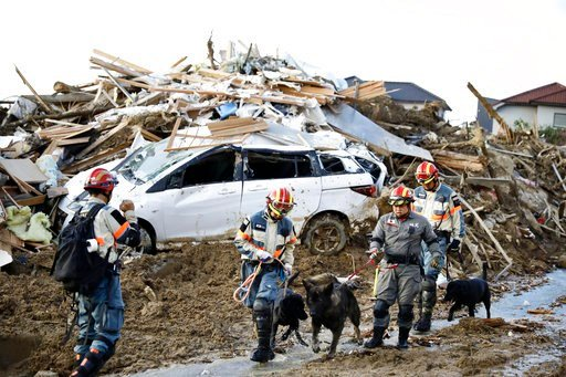 (Kyodo News via AP). Firefighters with rescue dogs search for missing people after heavy rain hit southwestern Japan, in Kumano town, Hiroshima prefecture, Monday, July 9, 2018. Rescuers in southwestern Japan dug up more bodies Monday as they searched ...