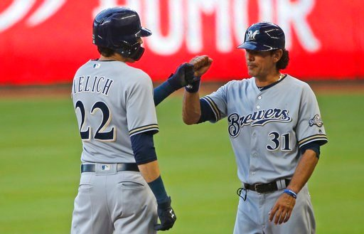 (AP Photo/Wilfredo Lee). Milwaukee Brewers' Christian Yelich (22) is congratulated by first base coach Carlos Subero (31) after getting a base hit during the first inning of a baseball game against the Miami Marlins, Monday, July 9, 2018, in Miami.