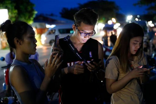(AP Photo/Vincent Thian). People check their mobile phones for update while waiting at a military airbase during emergency helicopter evacuation in Chiang Rai province, northern Thailand, Monday, July 9, 2018.