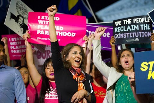 (AP Photo/Cliff Owen). Neera Tanden, president, Center for American Progress, center, rallies in front of the Supreme Court in Washington, Monday, July 9, 2018, after President Donald Trump announced Judge Brett Kavanaugh as his Supreme Court nominee.