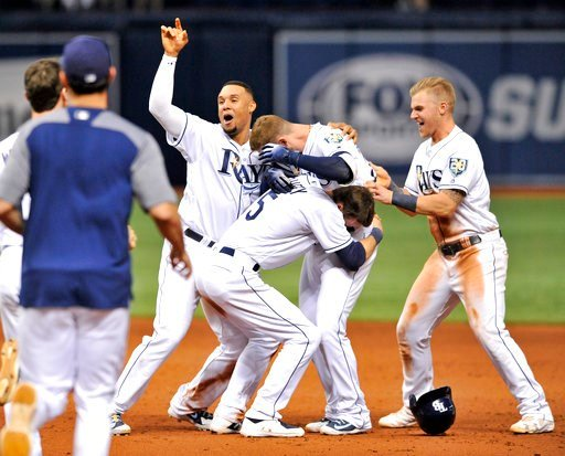 (AP Photo/Steve Nesius). Tampa Bay Rays' Carlos Gomez, left, Matt Duffy (5) and Jake Bauers, right, celebrate with Daniel Robertson, center, after his walk-off RBI-single off Detroit Tigers reliever Blaine Hardy during the 10th inning of a baseball gam...