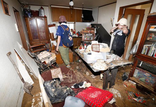 (Kyodo News via AP). Residents return to their house and look at the damage after heavy rain hit southwestern Japan, in Kure, Hiroshima prefecture, Monday, July 9, 2018. Rescuers in southwestern Japan dug up more bodies Monday as they searched for doze...
