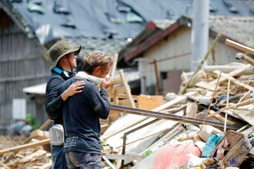 (Takuto Kaneko/Kyodo News via AP). Relatives react to a landslide site where three people were killed, after heavy rain hit southwestern Japan, in Uwajima, Ehime prefecture, Monday, July 9, 2018. Rescuers in southwestern Japan dug up more bodies Monday...