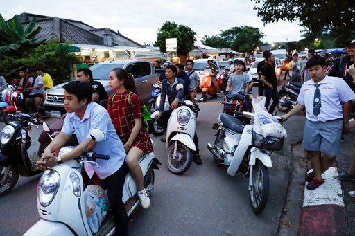 (AP Photo/Vincent Thian). People wait as police block the road during an emergency helicopter evacuation in Chiang Rai as divers evacuated some of the 12 boys and their coach trapped at Tham Luang cave in the Mae Sai district of Chiang Rai province, no...