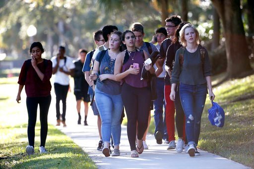 (AP Photo/Wilfredo Lee, File). FILE - In this Wednesday, Feb. 14, 2018 file photo, groups of students leave Marjory Stoneman Douglas High School in Parkland, Fla. Students and teachers at a Florida high school where a gunman killed 17 told investigator...
