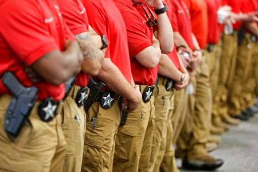 (Jim Damaske/The Tampa Bay Times via AP). Pinelas Sheriff's Department trainers line the back of the room during the beginning of training for the new Pinellas County School security officers Monday, July 2, 2018 at the Pinellas County Sheriff's Office...