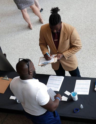 (AP Photo/Lynne Sladky). In this Thursday, June 21, 2018 photo, Gregory Johnson fills out an application for Custom Services at a job fair hosted by Job News South Florida, in Sunrise, Fla. On Tuesday, July 10, the Labor Department reports on job openi...