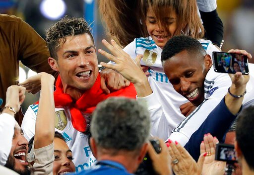 (AP Photo/Sergei Grits, File). FILE - In this Saturday, May 26, 2018 file photo Real Madrid's Cristiano Ronaldo celebrates with fans after winning the Champions League Final soccer match between Real Madrid and Liverpool at the Olimpiyskiy Stadium in K...