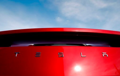 (AP Photo/David Zalubowski, File). FILE - In this April 15, 2018, file photo, the sun shines off the rear deck of a roadster on a Tesla dealer's lot in the south Denver suburb of Littleton, Colo. Electric car producer Tesla says it will build its first...