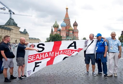 (AP Photo/Alexander Zemlianichenko). England soccer fans pose for a photo with their clubs banner in Red Square during the 2018 soccer World Cup in Moscow, Russia, Tuesday, July 10, 2018.