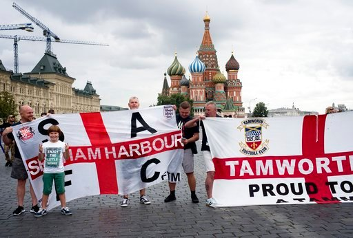 (AP Photo/Alexander Zemlianichenko). England soccer fans pose for a photo with their club banners in Red Square during the 2018 soccer World Cup in Moscow, Russia, Tuesday, July 10, 2018.