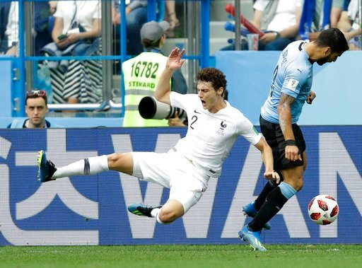 (AP Photo/Natacha Pisarenko). France's Benjamin Pavard, left, takes a tumble as he competes for the ball with Uruguay's Luis Suarez during the quarterfinal match between Uruguay and France at the 2018 soccer World Cup in the Nizhny Novgorod Stadium, in...