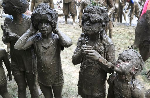 (AP Photo/Carlos Osorio). Girls line up to be judged Mud Day Queen during Mud Day at the Nankin Mills Park, Tuesday, July 10, 2018, in Westland, Mich. The annual day sponsored by the Wayne County Parks takes place in a 75' x 150' giant mud pit that giv...