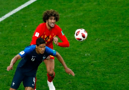 (AP Photo/Pavel Golovkin). France's Raphael Varane, left, duels for the ball with Belgium's Marouane Fellaini during the semifinal match between France and Belgium at the 2018 soccer World Cup in the St. Petersburg Stadium in St. Petersburg, Russia, Tu...
