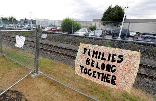 """(AP Photo/Ted S. Warren). A sign that reads """"Families belong Together"""" hangs on a fence outside the Northwest Detention Center in Tacoma, Wash., Tuesday, July 10, 2018. The Trump administration rushed to meet a deadline Tuesday for reuniting dozens of ..."""