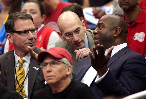 (AP Photo/Mark J. Terrill, FIle). FILE - In this May 11, 2014, file photo, NBA Commissioner Adam Silver, center, talks with Magic Johnson, right, as Kiki Vandeweghe looks on as they watch the Los Angeles Clippers play the Oklahoma City Thunder in the f...