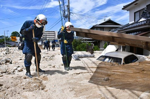 (Shingo Nishizume/Kyodo News via AP). Police use sticks during a search operation at a mud-covered area in the aftermath of heavy rains in Kure, Hiroshima prefecture, southwestern Japan, Wednesday, July 11, 2018. Rescuers were combing through mud-cover...
