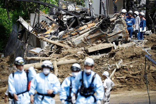 (Kota Endo/Kyodo News via AP). Rescuers work at a mudslide area during a search operation in Kumano town, Hiroshima prefecture, southwestern Japan, Wednesday, July 11, 2018. Rescuers were combing through mud-covered hillsides and along riverbanks Tuesd...