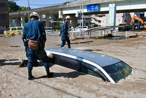 (Shingo Nishizume/Kyodo News via AP). A police officer looks into a car buried in mud during a search operation in the aftermath of heavy rains in Kure, Hiroshima prefecture, southwestern Japan, Wednesday, July 11, 2018. Rescuers were combing through m...