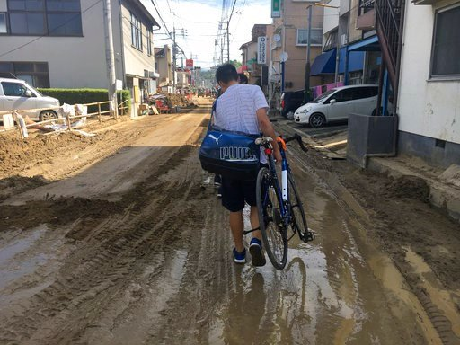 (AP Photo/Haruka Nuga). A man carries his bicycle on a mud-covered street in Hiroshima, southwestern Japan, Wednesday, July 11, 2018. Rescuers were combing through mud-covered hillsides and along riverbanks Tuesday searching for dozens of people missin...