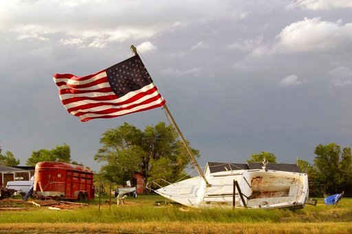 (Taylor Ordahl/Brooks Photography via AP). This Monday, July 9, 2018, evening photo, provided by Brooks Photography, shows a boat tilted with a flag still standing on its mast after a thunderstorm in Plentywood, Mont.