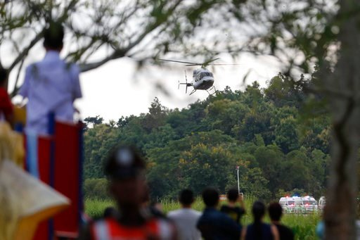 (AP Photo/Vincent Thian). Locals watch a helicopter believed to be carrying one of the boys rescued from the flooded cave, lands in Chiang Rai as divers continue to extract the remaining boys and their coach trapped at Tham Luang cave.